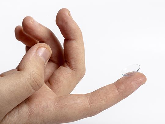Na imagem aparece um fundo branco e o close de uma mão, com uma lente de contato apoiada no dedo indicador.