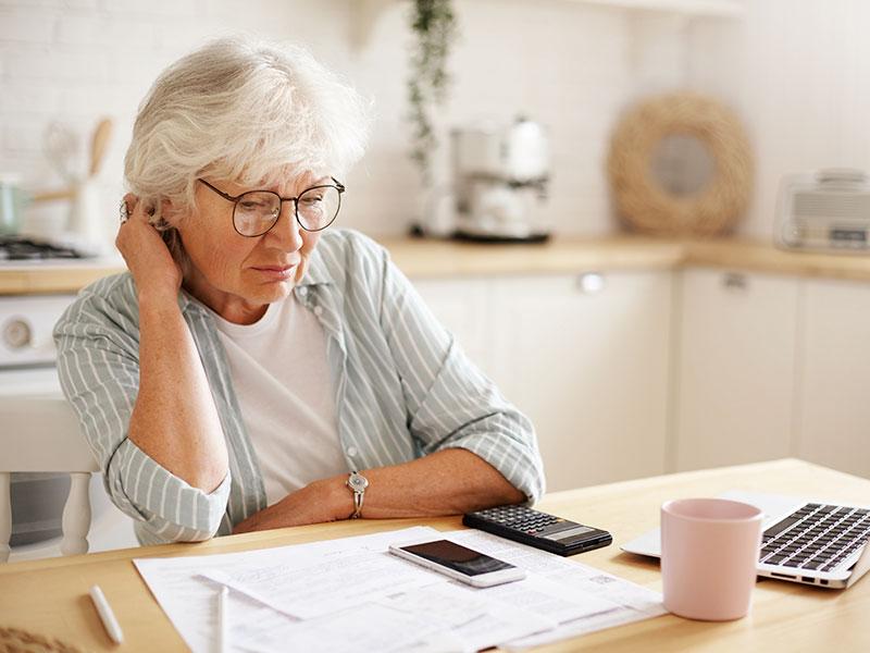 Imagem de uma mulher de meia idade, sentada à mesa na cozinha, vestindo uma camisa listrada, com cabelos brancos e óculos. Ela está com semblante triste enquanto olha pra mesa que contém um notebook, celulares e papeis.