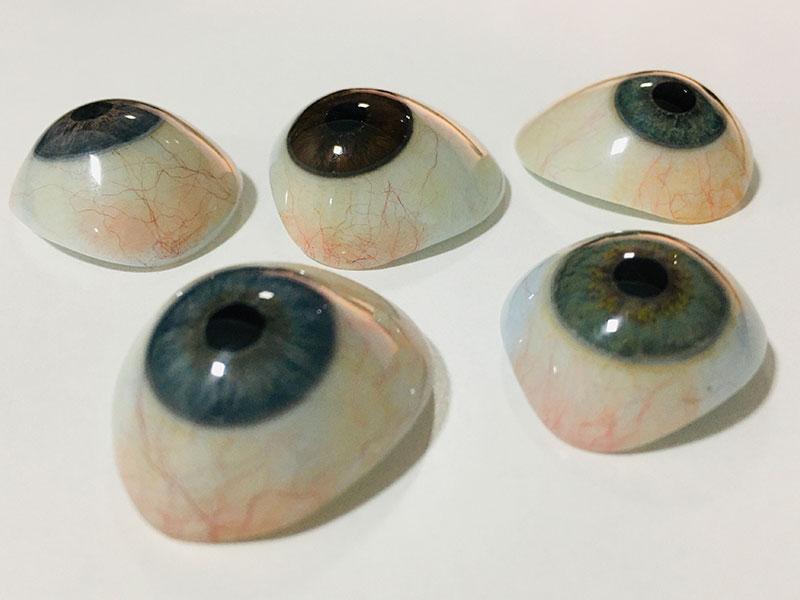 Cinco próteses oculares estão sendo exibidas sob uma base branca. A esquerda da imagem está um par de próteses azuis, ao centro apenas uma em tom castanho e, a direita, um par de próteses verdes.