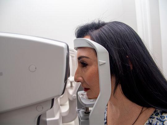 Na foto aparece uma paciente realizando o exame de tonometria. Ela tem cabelos pretos longos, pele branca, está vestindo uma blusa estampada, e aparece de perfil, com a cabeça apoiada no aparelho chamado tonômetro.